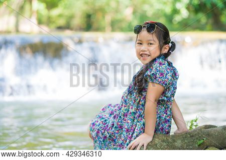 Little Girl Sitting On The Root Tree And Enjoying Waterfall Landscape. Traveling Nature Near A Beaut
