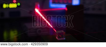 Experiment in optic lab with laser device. Red laser on optical table in physics laboratory