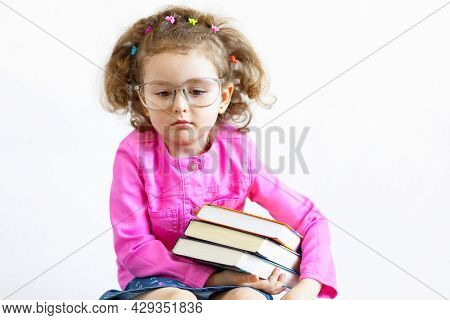Serious, Brooding, Sad, Distracted, Cute Smart Little Girl In Funny Big Glasses Reading A Stack Of P