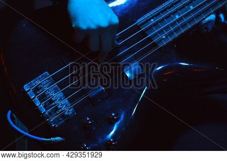 The Bass Player Plays On Black Five-string Bass Guitar In The Spotlight. Selective Focus