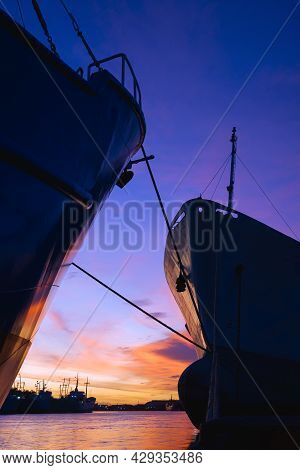 Silhouette 2 Oil Tankers Moored At Port With Many Vessels In Riverbank Area Against Colorful Twiligh