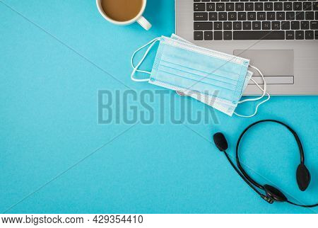 Top View Photo Of Two Medical Facemasks On Laptop Headset And Cup Of Drink On Isolated Pastel Blue B