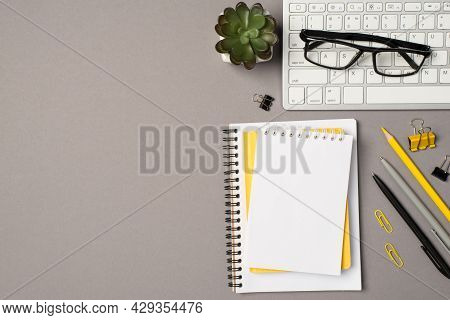 Top View Photo Of Workstation Glasses On Keyboard Flowerpot Stationery Binder Clips Pencil Pens And
