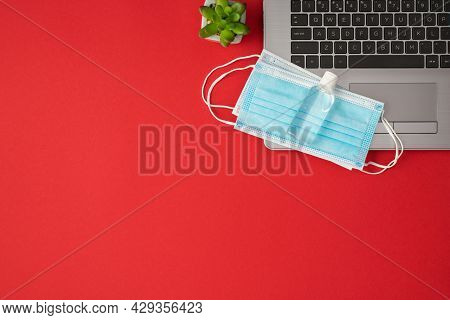 Top View Photo Of Transparent Sanitizer Bottle Two Medical Facemasks On Laptop And Plant On Isolated