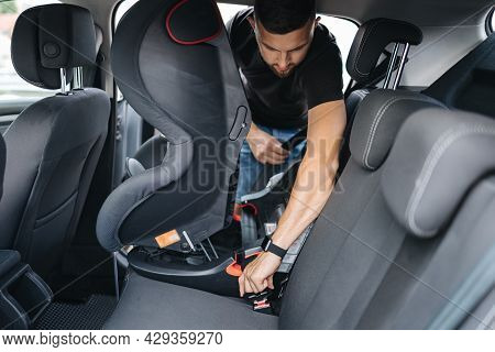 Man Installs A Child Car Seat In Car At The Back Seat. Responsible Father Thought About The Safety O