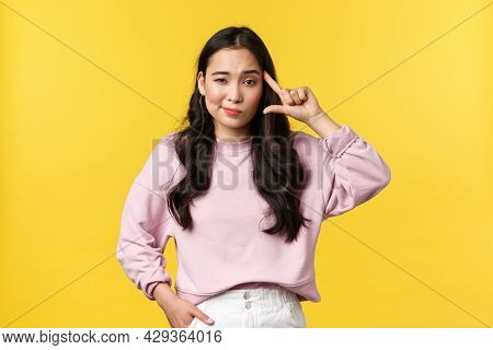 People Emotions, Lifestyle And Fashion Concept. Skeptical Asian Girl Rolling Finger Over Temple And