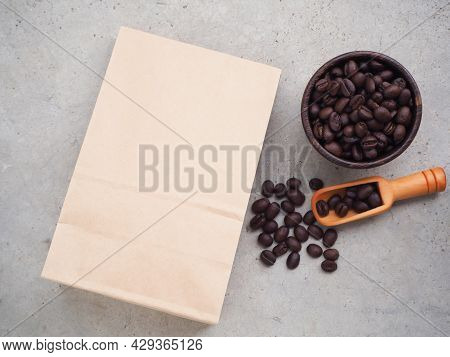 Brown Kraft Paper Bag With Coffee Beans In Wooden Bowl, Scoop On Grey Background. Top View With Copy
