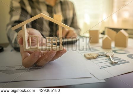 Bank Officer Or Realtor House Agents Showing Miniature House Model On The Desk With House Designs Do