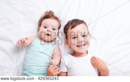 Happy Little Brother Hugs His Little Sister Lying On A White Blanket