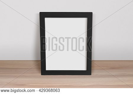 8x10 Black Frame Mockup Resting On A Scandinavian Wood Table. Features Clipping Path Inside Frame.
