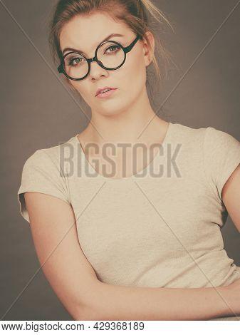 Bored Focused Or Grumpy Blonde Teenage Woman Wearing Nerdy Eyeglasses, White T Shirt. Teenager Fashi