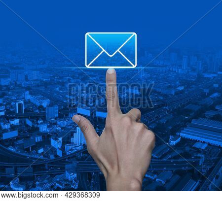 Hand Pressing Email Flat Icon Over Modern City Tower, Street, Expressway And Skyscraper, Business Co