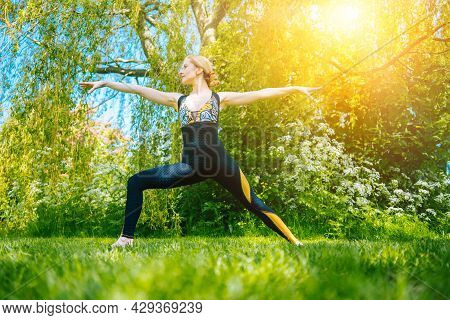 Young Woman Doing Yoga Asana In Park. Girl Stretching Exercise In Yoga Position. Happy And Healthy W