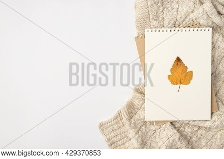 Top View Photo Of Yellow Autumn Leaf On Notebooks And Knitted Pullover On Isolated White Background