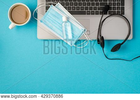 Top View Photo Of Two Medical Facemasks And Transparent Sanitizer Bottle On Laptop Headphones And Cu