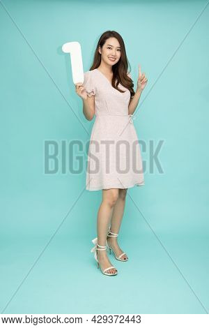 Young Beautiful Asian Woman Showing Number 1 And Pointing Up With Finger Number One Isolated On Gree