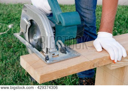A Man Builder With A Circular Saw Cuts A Board At The Construction Site Of A New House. Carpenter Ha