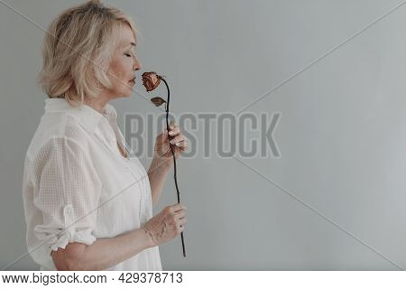 Sad Elderly Senior Woman In White Shirt Holds Withered One Dry Old Dead Rose Flower. Old Age And Agi