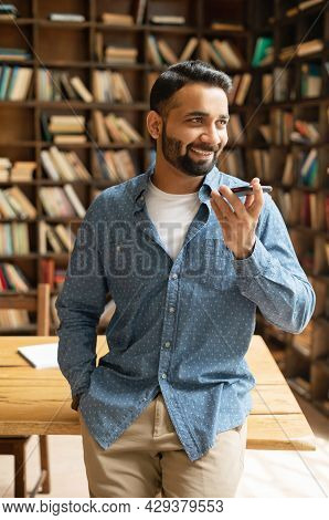 Vertical Portrait Of Indian Man In Smart Casual Wear Recording And Sending Voice Message, Mixed Race