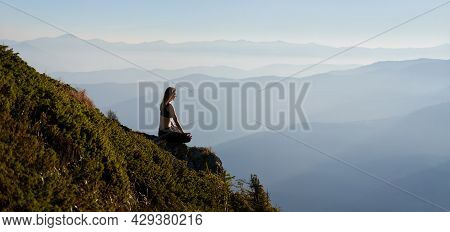 Fit Young Woman Sitting On Grassy Hill In Lotus Position While Mediating Outdoors In The Morning. Sp