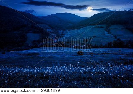 Mountainous Countryside Landscape At Night. Pastures And Rural Fields Near The Forest On The Hills.