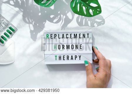 Text Replacement Hormone Therapy On Light Box In Hand. Menopause, Rht Therapy Concept. Estrogen Repl