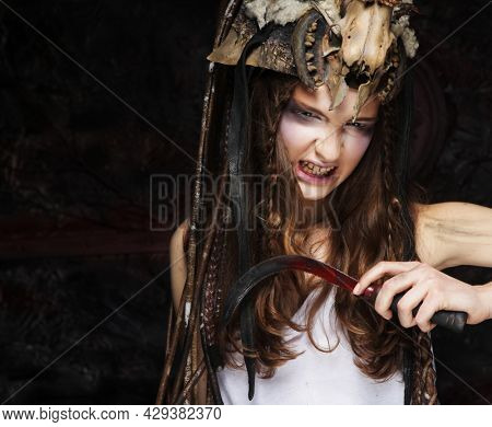 Young witch holding sickle. Bright make up, skull, smoke- halloween theme. Studio shot.
