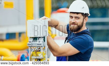 Electrician In A Helmet And Overalls Works Adjusts The Equipment Looks Into The Camera And Smiles. A