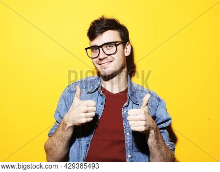 Portrait of cheerful man in basic clothing and eyewear smiling and showing thumbs up at camera isolated over yellow background