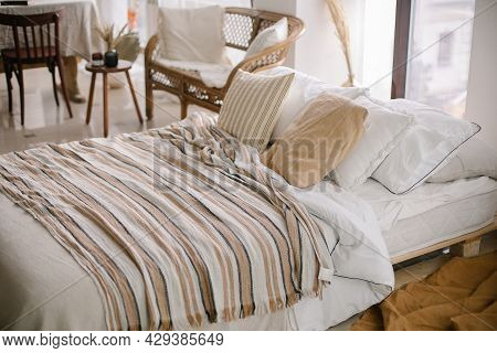 Cozy Bedroom. Bed With Pillows And Striped Blanket At Cozy Light Bedroom