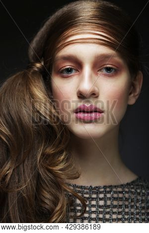 Beautiful woman with make up in pink tones. Girl model with braided braid over black background. Hairstyle in the trend. Beauty, fashion, cosmetics and cosmetology.