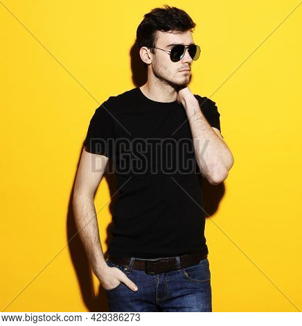 Portrait of handsome smiling stylish hipster lambersexual model.Man dressed in black T-shirt and jeans. Fashion male posing on yellow background in studio in sunglasses.