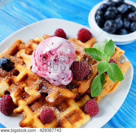 Belgian waffles with fresh berries and ice cream over wooden background. Top view.