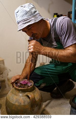 Man Making Pickles In A Ceramic Vasel Using An Old Recipy. He Enriches The Contents Of The Vessel Wi