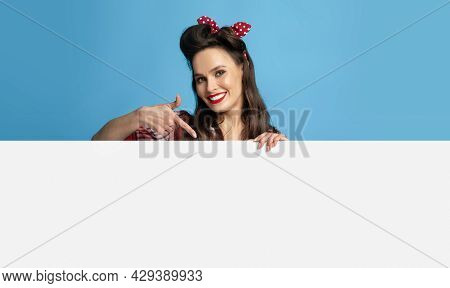 Happy Pinup Lady Pointing At Blank Banner, Smiling At Camera On Blue Studio Background, Mockup For D