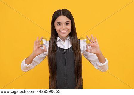 Happy Girl Child In School Uniform Smile Gesturing Double Ok Sings Yellow Background, Okay