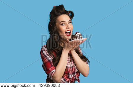 Charming Pinup Lady In Retro Wear Eating Chocolate Cake On Blue Studio Background