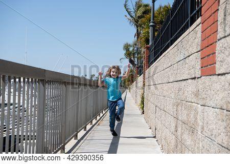 Break Free. Energetic Child Run On Promenade. Happy Boy Enjoy Free Time. Having Fun. Summer Vacation