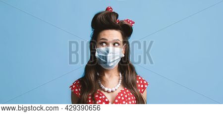 Young Pinup Lady In Retro Dress Wearing Face Mask Against Covid-19, Looking Aside At Blank Space On