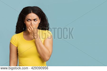 African American Woman Closing Nose With Fingers, Feeling Unpleasant Scent, Standing Over Blue Backg