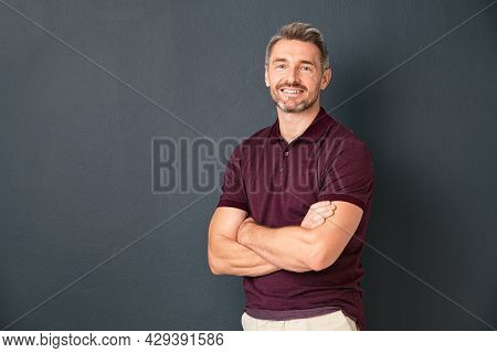 Portrait of smiling mature man standing on gray wall with folded arms. Successful mid adult man with folded arms standing over grey background while looking at camera with copy space.