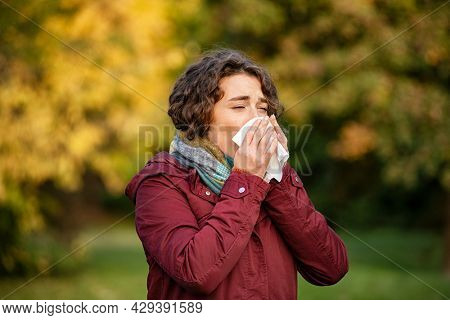 Woman coughing and blowing her nose in park during autumn season. Sick young woman with nose wiper caught cold. Girl blowing in a tissue in a cold autumn day.