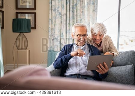 Happy old couple sitting on sofa using digital tablet. Cheerful senior man and elderly woman relaxing at home while watching funny video on digital tablet. Grandparents making a video call, lockdown.