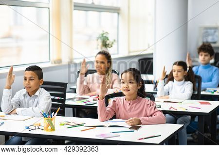 Diverse Group Of Little Schoolchildren Raising Hands At Classroom
