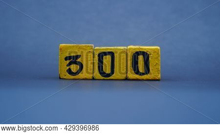 Wooden Block With Number 300. Yellow Color On Dark Background. Focus Selected