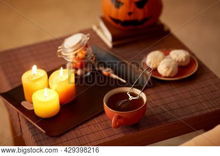 drinks, holidays and leisure concept - mesh tea infuser ball in ceramic mug at home on halloween
