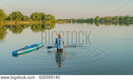 male paddler with a paddle and a racing stand up paddleboard, summer scenery on a calm lake in Colorado,