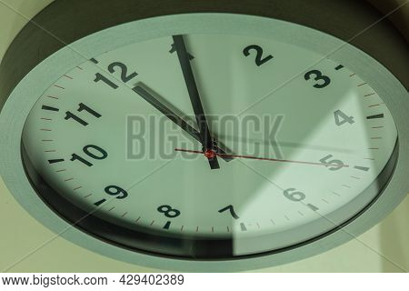Modern White Wall Clock Shows The Time 5 After 12. Close Up To A Wall Clock In Sunlight With Shadows