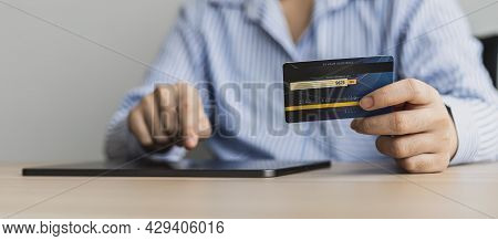 A Woman Typing On A Tablet And Holding A Credit Card, She Fills In Her Credit Card Information On A