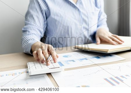 A Businesswoman Presses On A White Calculator And Looks At The Numbers From A Notebook She Notes Dur